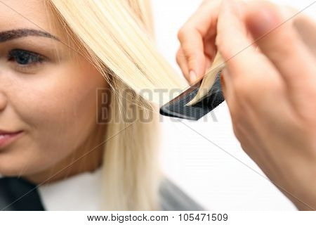 Hairdresser combing woman