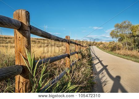 wooden fence with a shadow and a  bike trail  - Poudre River Trail in northern Colorado near Windsor. It is a  paved path  extending more than 20 miles between Timnath and Greeley.