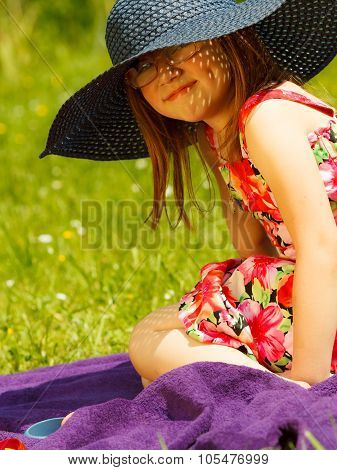 Cute little girl wearing big summer hat pretending to be woman lady. Child imitate mother playing in park outdoors poster