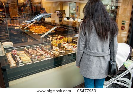 Single Mother Admiring French Sweet Pastry In Bakery Window