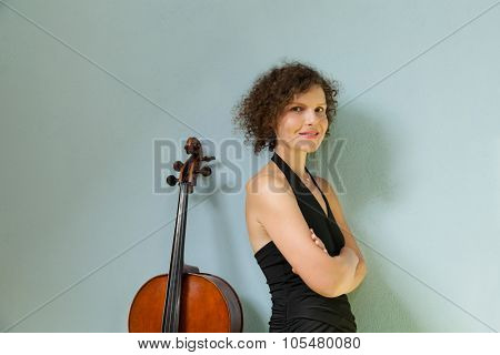 Portrait of young cellist, wall background
