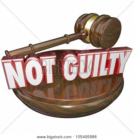 Not Guilty words in 3d letters on a wood judge gavel or block as a verdict in a court case acquiting the defendent in a case or trial