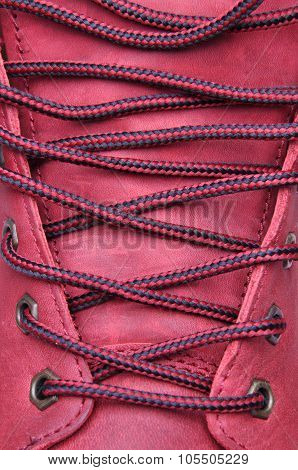Binding laces in the shoe with a red leather closeup