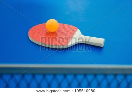 Pingpong Racket And Ball And Net On A Blue Pingpong Table