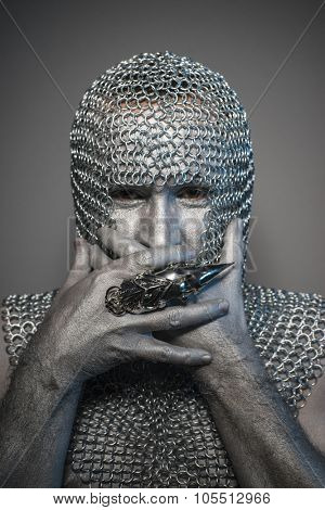 Battle, man in chain mail and leather painted silver, medieval warrior