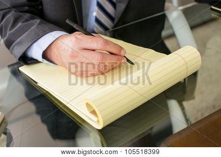 Closeup of man writing in a notebok