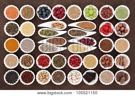 Health and diet superfood food selection in porcelain bowls over lokta paper background. High in vitamins and antioxidants.