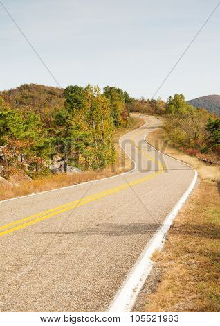 Talimena scenic byway winding on the crest of the mountain, with trees in fall colors