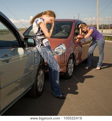 Car accident.Two sad women are standing by their smashed cars and waiting for help.Great auto insurance or car insurance photo