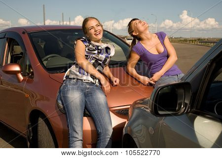 Car accident. Two young women are standing near the boonet of the smashed car and smiling.Great auto insurance or car insurance photo.
