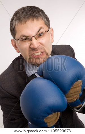 Aggressive businessman with boxing gloves isolated on white background
