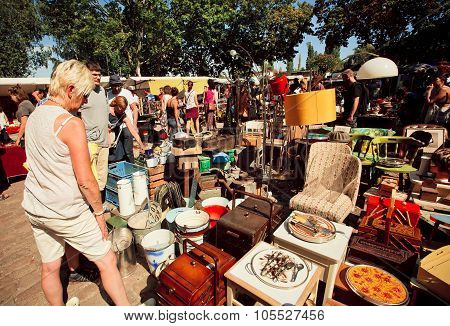 Flea market with people choosing vintage furniture