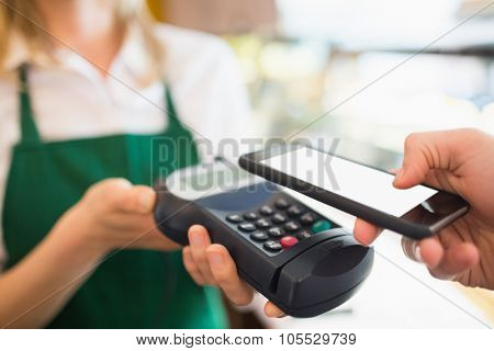 Cropped image of female worker accepting payment from customer through NFC in bakery poster
