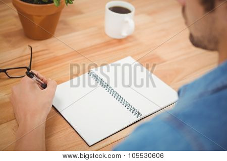 Cropped image of hipster holding pen with spiral book and coffee on table in office