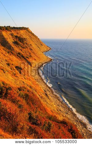 View of a steep winding coastline and beach at sunset or sunrise with the glow of the sun low over the horizon of the ocean illuminating the terrain Cape Emine Bulgaria poster