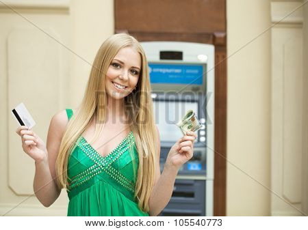 Young beautiful woman in a green dress is holding a cash dollars on the background of the ATM in a shopping center