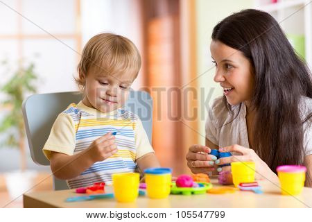 child boy and woman play colorful clay toy at nursery or kindergarten