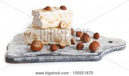 Sweet nougat with hazelnuts isolated on white
