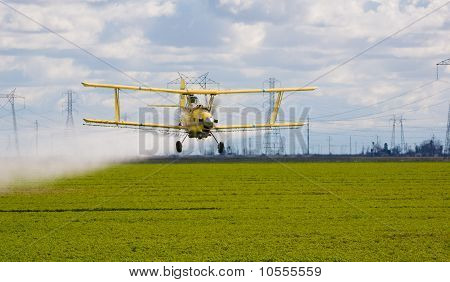 crop duster spraying insecticide on crops in central California poster