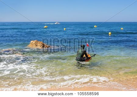 Underwater Hunter In The Water Preparing To Dive. Underwater Fishing In The Atlantic Ocean.