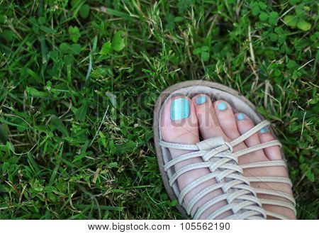 The woman feet standing on the green grass