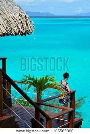 Female Tourist On The Balcony Of An Overwater Bungalow
