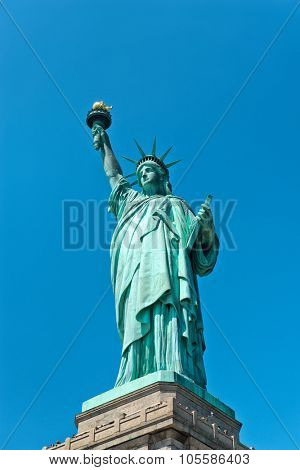 Low angle close up view of the iconic copper covered Statue of Liberty at the entrance to New York harbour holding aloft her torch against a clear blue sky in a tourism and travel concept