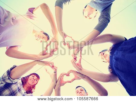 a group of people with their hands in a circle making heart shapes toned with a retro vintage instagram filter app or action effect