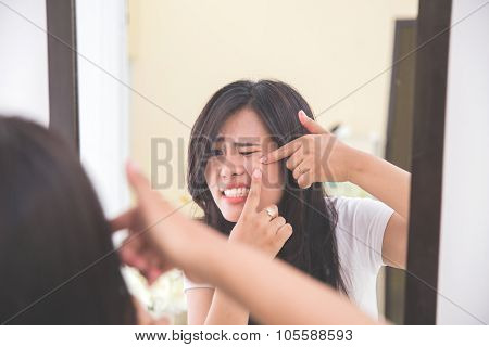 Woman Squeezing Pimples Look At The Mirror