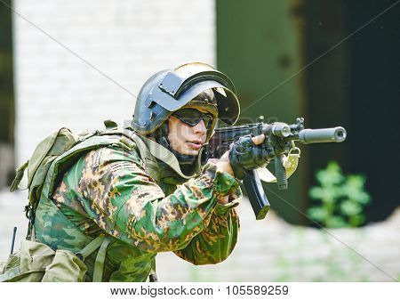 military. soldier with assault rifle in uniform patrolling territory outdoors