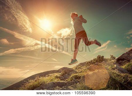 Female running in mountains under sunlight.