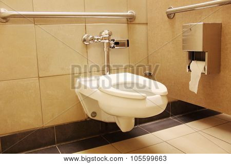Clean white porcelain toilet with rails for handicap
