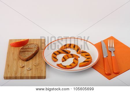 Grilled pumpkin hokkaido on white plate with toasted bread on wooden board with orange fork and knife on orange napkin on white poster