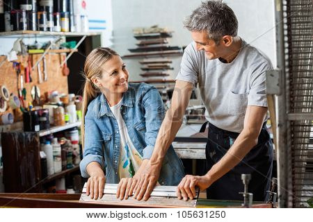 Happy male and female workers looking at each other while using squeegee in factory