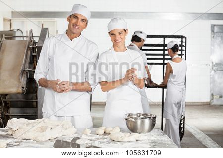 Portrait of smiling male and female Baker's making dough balls while colleagues working in background at bakery