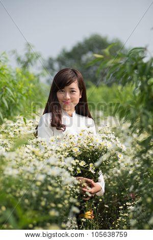 Vietnamese girl in traditional dress in white daisy flower garden