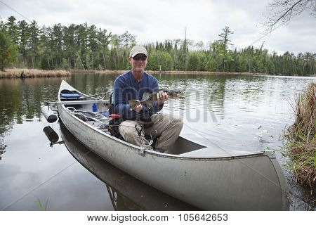 Fisherman In A Canoe On A Lake Shows A Walleye
