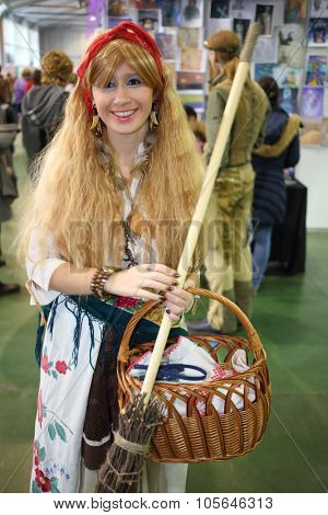 MOSCOW - OCT 12, 2014: A girl dressed as Baba Yaga with a broom at the EveryCon 2014 in the exhibition center Sokolniki