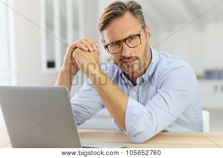 Handsome 40-year-old man at home using laptop