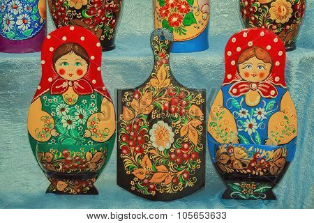 Traditional Russian Souvenirs: matryoshka dolls and kitchen boards decorated with ornaments. poster