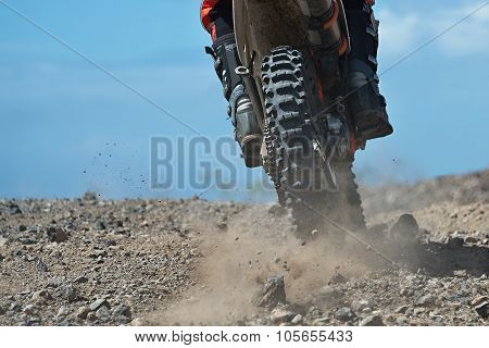 motocross racer accelerating in dirt track
