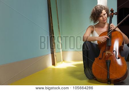 Portrait of young cellist, interior