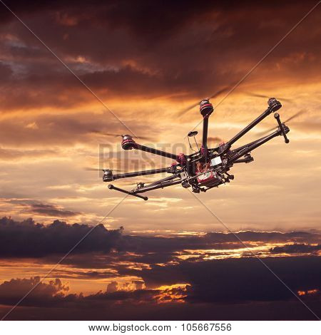 Flying copter with their gear on the background of a beautiful sunset. poster