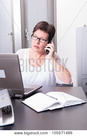 Woman In Her Homeoffice On The Phone