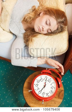 Exhausted woman waking up in bed turning off alarm clock. Young girl in the morning. poster