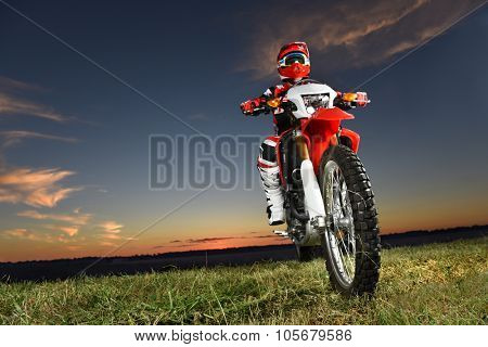 Man riding motocross motorcycle at sunset - With copy space