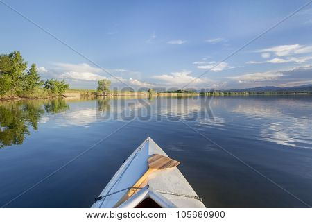 decked canoe bow with a paddle on a calm lake - Lonetree Reservoir near Loveland, Colorado
