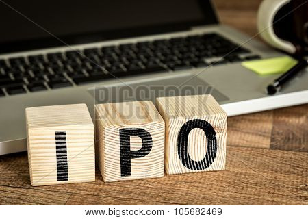 IPO (Initial Public Offering) written on a wooden cube in front of a laptop