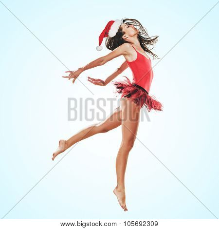 Young dancer woman in christmas hat jumping on a blue background. Healthy athletic woman is practicing dancing moves and jumps in the studio. Professional ballet dancer. Christmas lifestyle concept