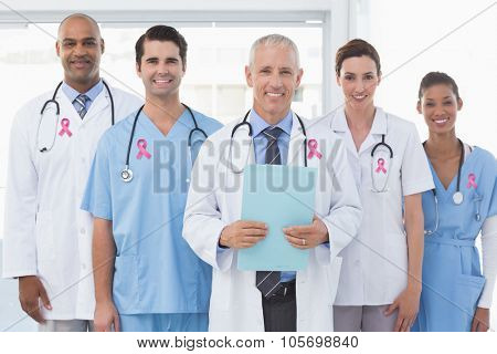 Pink breast cancer awareness ribbon against team of smiling doctors looking at camera